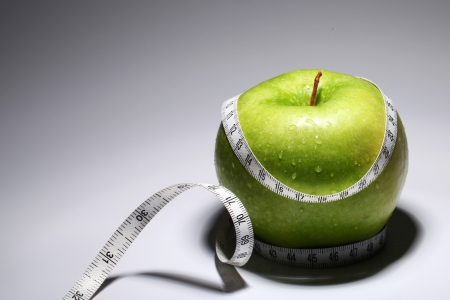 Fresh green apple with measure tape  over gray gradient Stock Photo - 14362846