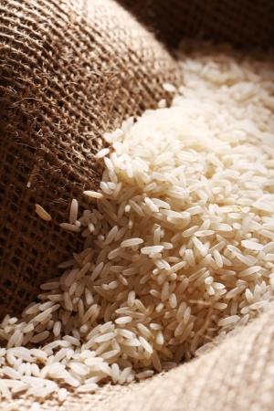 arroz blanco: Cierre de granos de arroz blanco en la tela bolsa Foto de archivo