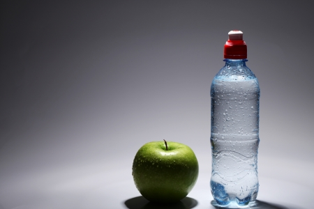 Bottle of fresh cold water and green apple over gray background photo
