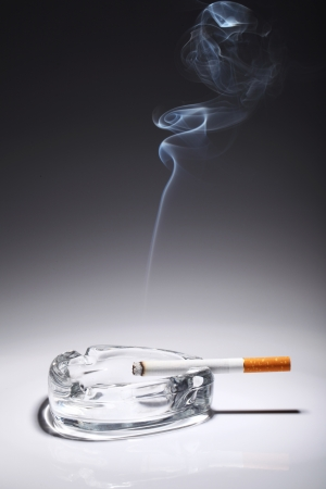 ashtray: Cigarette in the ashtray over gray gradient Stock Photo
