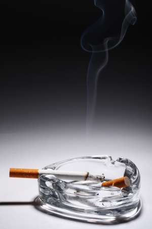 Cigarette in the ashtray over gray gradient photo