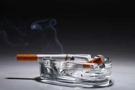pernicious: Cigarette in the ashtray over gray gradient Stock Photo