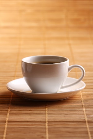 Cup of hot coffee on wooden surface photo