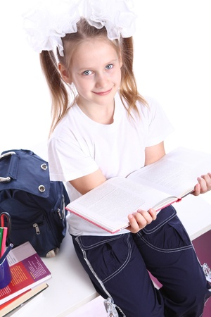 Cute little girl with schoolbag sitting on the desk photo