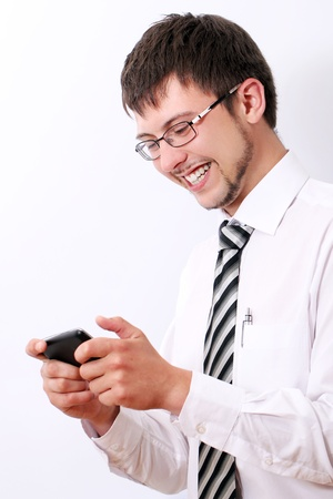 Young and happy businessman typing sms on his cellphone photo