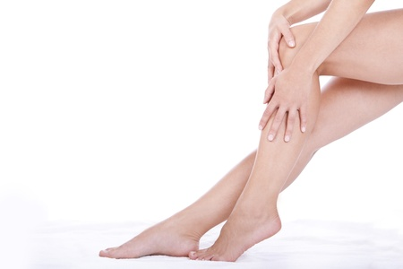 long sexy legs: Woman applying moisturizer cream on the legs  over white background