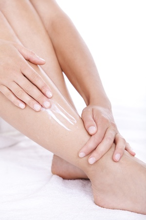 Woman applying moisturizer cream on the legs  over white background photo