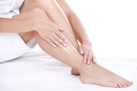 leg massage: Woman applying moisturizer cream on the legs  over white background