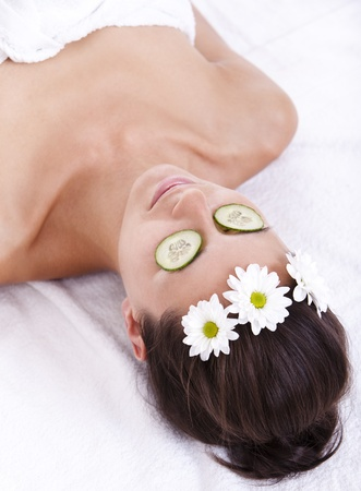 Woman relaxing with cucumber slices over her eyes photo