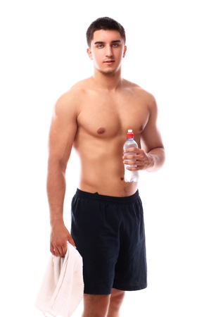 Muscular guy with towel and bottle of water over white background photo