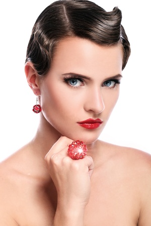 Young and beautiful woman with red jewelry over white background photo