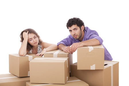 Tired young couple with cardboard boxes over white background photo