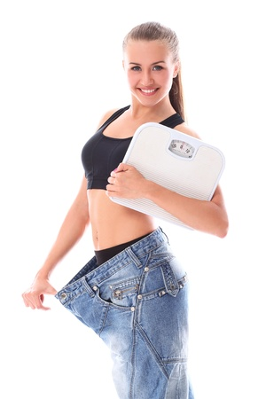 Woman wearing old jeans after weight loss over white background photo