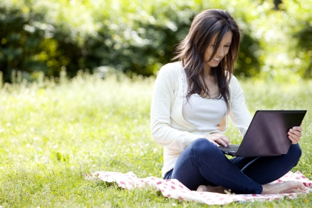 Young and happy girl with laptop in the park photo