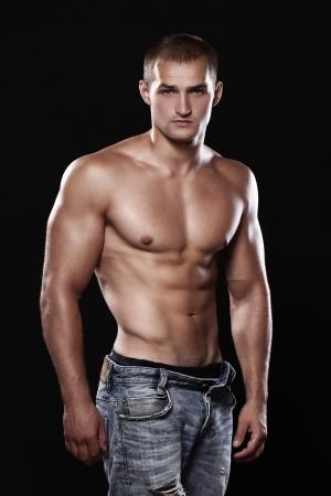 желудок: Молодые и сексуальные парень джинсах на черном фоне