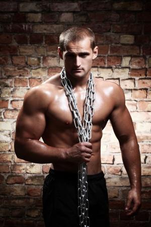nude boy: Muskul�s Kerl mit Ketten auf seinen Schultern gegen die Wand Lizenzfreie Bilder