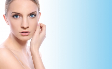 Beautiful woman with clean face over blue background photo