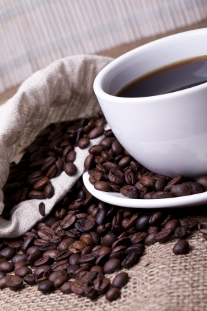 Cup of hot coffee over cloth sack photo