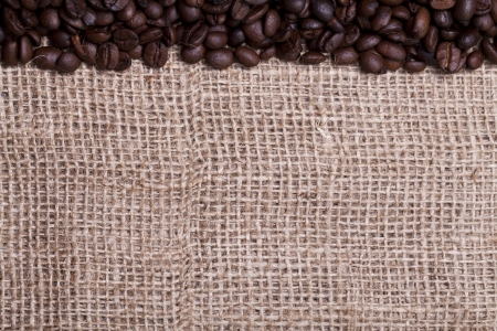 Coffee beans over cloth sack texture photo