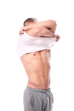 muscle shirt: Tipo muscular quitaba la camisa sobre bacground blanco