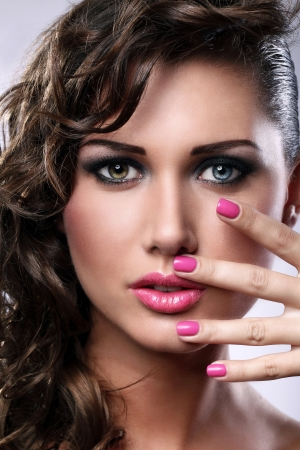 Portrait of young woman with bright make-up and manicure photo