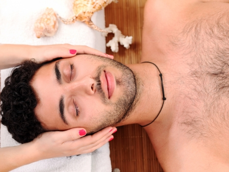 Young and handsome guy enjoying massage therapy photo