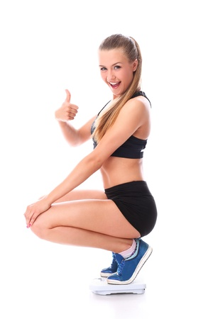 Happy fitness girl on the scales with thumb up over white background