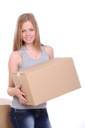 cajas de carton: Mujer joven que lleva caja de cart�n sobre fondo blanco Foto de archivo