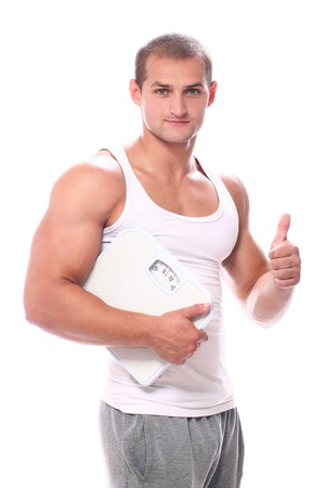 Happy muscular guy with scales over white background photo