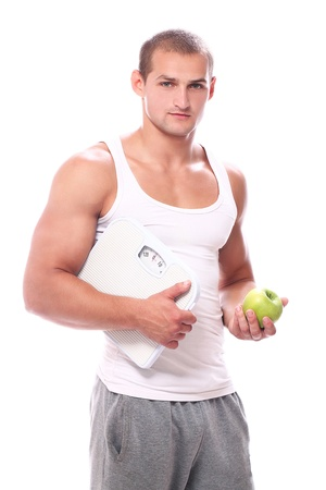Muscular guy with scales and green apple over white background photo