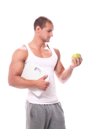 boy muscles: Muscular guy with scales and green apple over white background Stock Photo