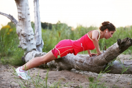 push: Young fitness woman doing push ups on the broken tree Stock Photo