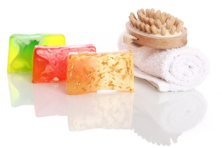 Natural soap with white towel and wooden brush over white background photo