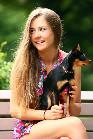 Young and happy girl with her cute dog sitting in the park photo