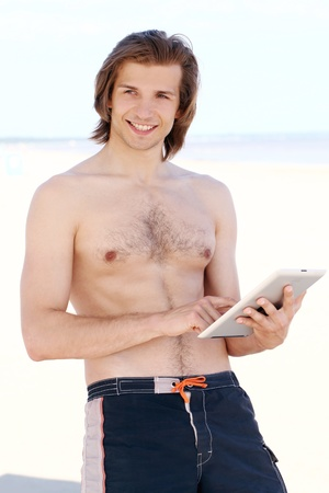 Happy handsome guy with a tablet pc on the beach photo