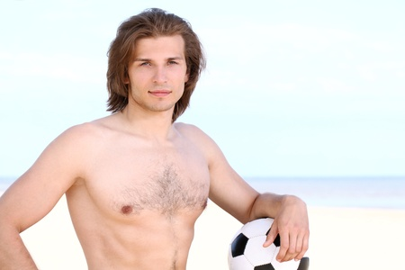 Young and handsome guy with soccer ball on the beach photo