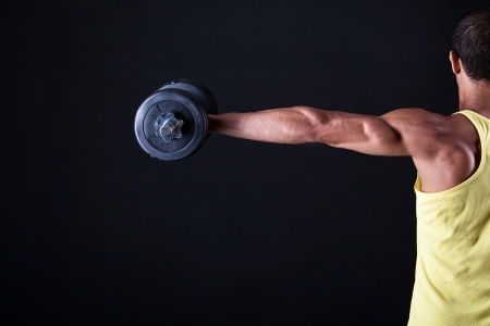 Strong and muscular guy with dumbbell over black background photo