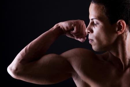 desnudo masculino: Hombre muscular que muestra su bíceps fuertes sobre fondo blanco