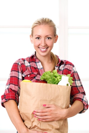 Happy smiling woman holding a grocery bag  photo