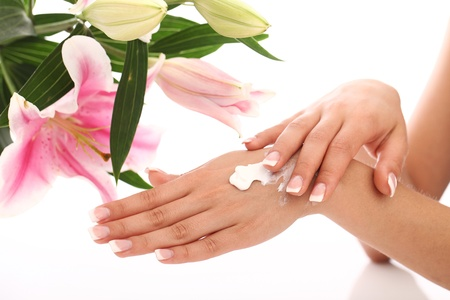 cosmetic cream: Woman applying cream on her beautiful hands