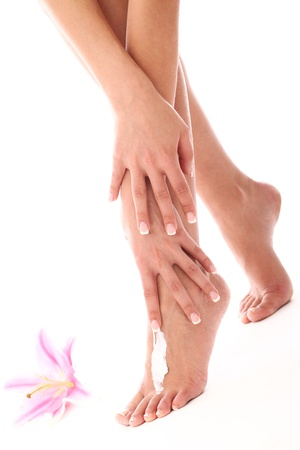 Woman applying cream on her legs over white background photo