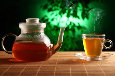 Hot green tea in glass teapot and cup on the table photo