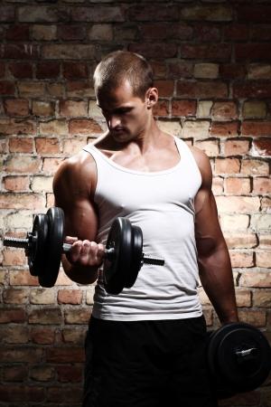 lift hands: Tipo muscular haciendo ejercicios con pesa contra una pared de ladrillo Foto de archivo
