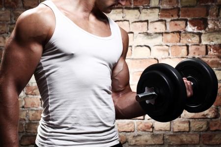 muskeltraining: Muscular guy �bungen mit Hantel gegen eine Mauer