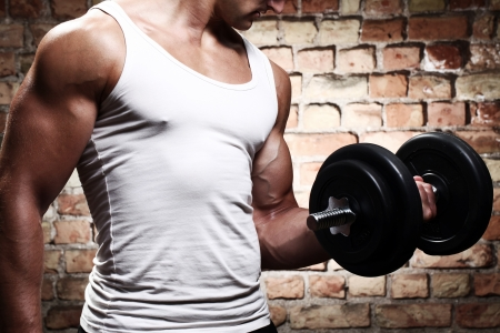 fit man: Muscular guy doing exercises with dumbbell against a brick wall Stock Photo