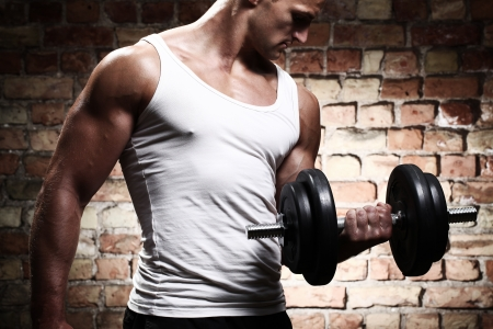 Muscular guy doing exercises with dumbbell against a brick wall photo