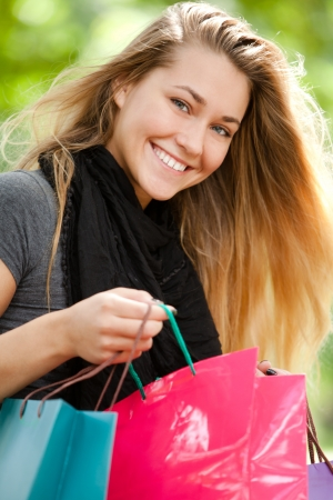 Happy woman with shopping bags in the park Stock Photo - 15184290