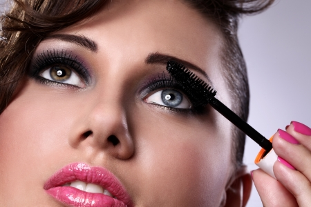 Close up of woman face with mascara brush  photo