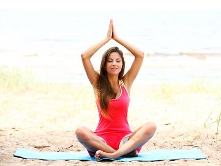 Young woman doing yoga exercises on the seaside Stock Photo - 15348185