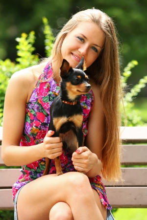 Young happy woman with her cute dog in the park photo